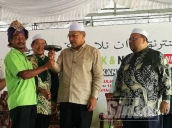 Ahmad (dua dari kanan) tertarik dengan gasing yang dipersembahkan sempena Hari Peladang, Penternak dan Nelayan Negeri Kelantan di Pantai Bisikan Bayu hari ini.