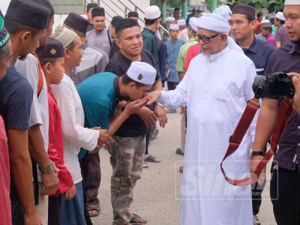 Abdul Hadi bersalaman dengan orang ramai selepas kuliah Dhuha di Masjid Rusila hari ini.