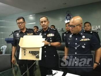 Mohamad Noor (tengah) menunjukkan pistol tiruan yang digunakan suspek ketika ditemui (IPD) Kuantan di sini hari ini.