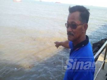 Abu Bakar menunjukkan perairan sekitar Jeti Tanjung Kling yang dicemari sisa arang batu dipercayai dari kapal negara Indonesia yang berlabuh di kawasan terbabit.