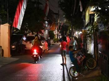 Penduduk tempatan keluar daripada kediaman masing-masing selepas Jakarta digegarkan dengan gempa berukuran 7.4 skala Richter. - Foto AFP