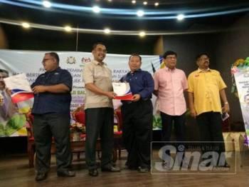 Pegawai Pertanian Johor Bahru, Azizul Hafiz Azizan menyampaikan anak pokok simbolik kepada salah seorang pengunjung yang hadir ke majlis tersebut, hari ini.