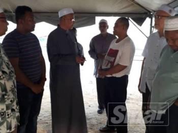 Wan Hassan (tiga dari kiri) melawat keluarga mangsa di Jeti A'king Kuala Dungun hari ini.