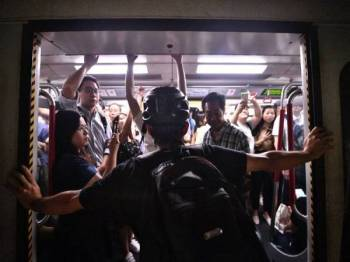 Seorang penunjuk perasaan menghadang pintu tren MTR di stesen Fortress Hill, Hong Kong. - Foto AFP