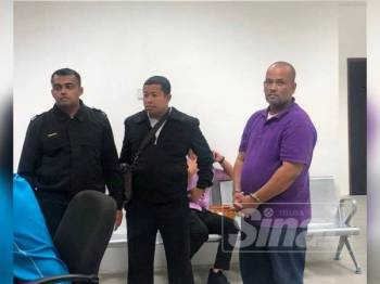 Tertuduh (kanan) dikawal anggota Suruhanjaya Pencegahan Rasuah Malaysia di lokap Mahkamah Kota Bharu hari ini.