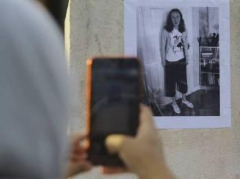 Seorang penduduk sekitar merakam gambar seorang pelancong dari Ireland, Nora Anne Quoirin, 15, yang dilekatkan di sekitar kawasan Kampung Pantai ketika tinjauan sekitar kawasan tersebut hari ini. - Foto Bernama