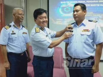 Timbalan Ketua Pengarah Logistik, Laksamana Madya Maritim Datuk Tan Kok Wee (tengah) memakaikan lencana kepada Sharizan (kanan) sambil disaksikan Wan Mat (kiri) pada Majlis Serah Terima Tugas Pengarah Maritim Negeri Perak di Ibu Pejabat APMM Perak, hari ini.