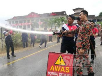 Pelajar diberi peluang mengendalikan hos bomba.