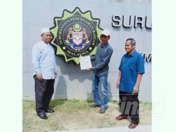 Bahaman (tengah) bersama dua lagi AJK Bersatu Bahagian Bagan Datuk menunjukkan salinan laporan serta bukti yang diserahkan kepada SPRM untuk siasatan berkaitan penjualan lembu korban.