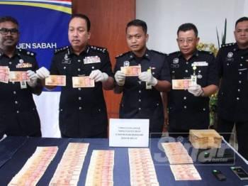Zaini (dua, dari kiri) menunjukkan wang kertas real 10,000 palsu yang dirampas di CIQ Tawau, Isnin lalu.
