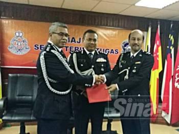 Aidi (tengah) menyaksikan penyerahan dokumen serah terima tugas Ketua Cawangan Khas Terengganu antara Asisten Komisioner Zakaria Haron (kiri) kepada Superintendan Zainol Ahmad di IPK Terengganu hari ini.