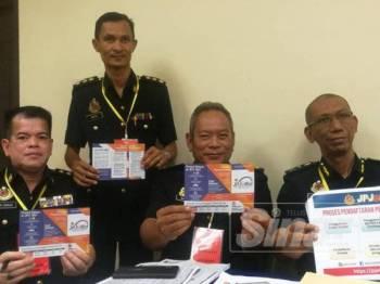 Mohamad (kanan) menunjukkan manual penggunaan aplikasi JPJeBid untuk memudahkan orang ramai membida nombor pendaftaran kenderaan.