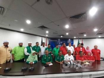 Ahmad Yunus (duduk, tiga dari kiri) dan Mat Nadzari (duduk, empat dari kiri) serta kepimpinan Pas dan UMNO pada sidang media selepas Mesyuarat Sekretariat Perpaduan Ummah antara Pas dan UMNO di Bangunan UMNO Selangor, hari ini.