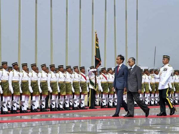 Perdana Menteri Tun Dr Mahathir Mohamad (dua, kanan) mengiringi Presiden Indonesia Joko Widodo memeriksa barisan kehormat daripada Batalion Pertama Rejiman Askar Melayu Diraja semasa sambutan rasmi di Dataran Perdana, Bangunan Perdana Putra pada lawatan rasmi Presiden Indonesia itu ke Malaysia hari ini. - Foto Bernama