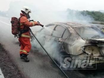 Anggota bomba berusaha memadamkan api pada sebuah kereta yang terbakar di Kilometer 146.4 Lebuhraya Pantai Timur (LPT) tengah hari tadi.