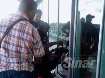 Polis memeriksa bahagian cermin tingkap Pejabat UMNO Pekan yang ditembak.