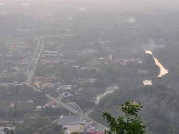 Pemandangan Tamparuli sebahagiannya diselubungi jerebu berpunca perbuatan segelintir penduduk melakukan pembakaran secara terbuka yang dirakam dari puncak Bukit Ruhiang Tamparuli lewat petang semalam. - Foto BERNAMA