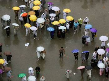 Para jemaah tiba di Mina di bawah hujan lebat untuk melaksanakan ibadah melontar jamrah pada Isnin. - Foto AFP/Abdel Ghani Bashir