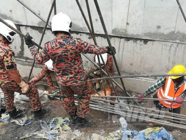 Anggota bomba menjalankan kerja mengalihkan timbunan besi cerucuk konkrit di tempat kejadian bagi mengeluarkan mangsa.