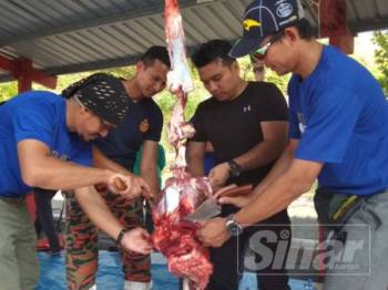 Dari kiri: Nizam, Sharudi, Rashidi dan Nassry Masdee melapah daging lembu pada program yang diadakan di Balai Bomba dan Penyelamat Meru Raya semalam.