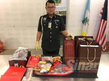 Pegawai penguatkuasa MAQIS menunjukkan produk daging yang dirampas di Lapangan Terbang Antarabangsa Bayan Lepas baru-baru ini.