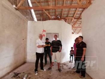 Raja Kamarul Bahrin Shah (kiri) meninjau masalah isu projek perumahan terbengkalai di Padang Setengge, Hulu Terengganu.