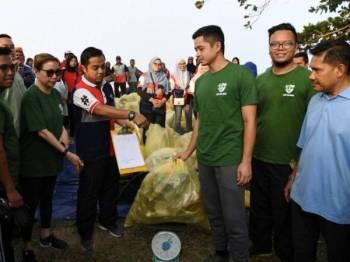 Pemangku Raja Pahang Tengku Hassanal Ibrahim Alam Shah Al-Sultan Abdullah (tiga, kanan) berkenan mencemar duli berangkat sama menimbang sampah yang dikumpul di sekitar Pantai Sepat bersama para peserta program pada Program Plogging Daerah Kuantan hari ini. Foto: Bernama