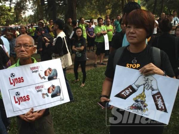 Peserta membawa plakad dan poster menyatakan bantahan terhadap keputusan kerajaan meneruskan Lynas.