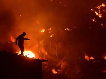 Seorang penduduk cuba memadamkan kebakaran yang melanda setinggan di kejiranan Mirpur, Dhaka Jumaat lalu. - Foto AFP