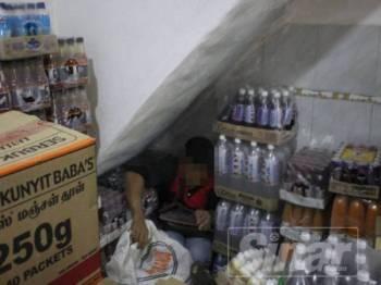 Lelaki warga Bangladesh cuba bersembunyi dibelakang timbunan kotak dan botol air.