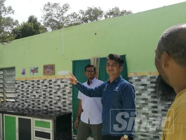 Faiz (dua dari kanan) melawat kediaman Mahazir Hassan di Kampung Tepi Laut yang rosak akibat dibadai ribut Lekima, Jumaat lepas.