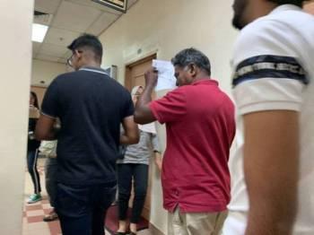 Nersaeman (baju merah) dibawa keluar dari kamar perbicaraan.
