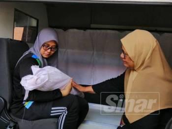Ahli keluarga sebak memangku jenazah Rafiq, 14 bulan, yang meninggal dunia bersama kedua ibu bapanya dalam kebakaran pagi tadi.