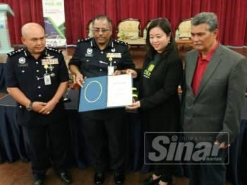 Ab Rashid (kiri) menyaksikan pertukaran dokumen Nota Kerjasama di antara Polis Kontinjen Selangor dengan PICKnGO antara Kumaran dengan Valerie.