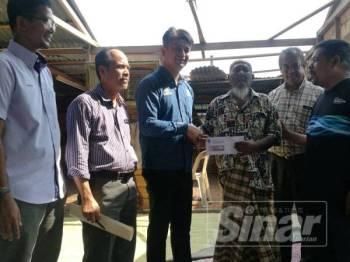 Faiz (tiga dari kiri) menyerahkan sumbangan kepada Azman Harun, 82, (tiga dari kanan) ketika melawat rumah warga emas itu di Kampung Tepi Laut hari ini.