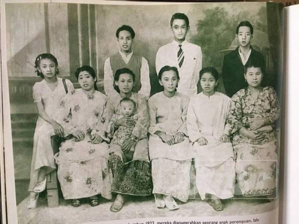 Tik (duduk, tiga dari kiri) bersama suami dan adik beradik yang lain.