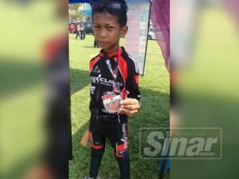 Muhammad Aqif menunjukkan pingat yang diperolehi selepas tamat menyertai acara kayuhan sejauh 30 kilometer dalam acara kayuhan TM Flyover International Ride.