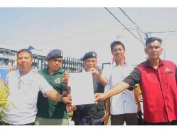 Zamri (tengah) bersama rakan-rakannya membuat laporan polis di IPD Pasir Mas berhubung kenyataan Yew Yin yang menghina anggota ATM.