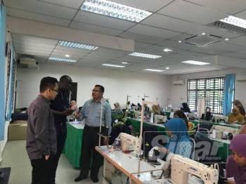 Syeikh Zakaria (kanan) menunjukkan Pusat Kemahiran Jahitan Zakat Kedah kepada Namungo (tengah) di Menara Zakat Negeri Kedah baru-baru ini.