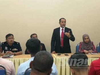Mohd Nurkhuzaini (tengah) ketika memberi penerangan mengenai larangan berniaga di lampu isyarat.