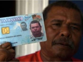 Mohd Merdeka Ismail menunjukkan kad pengenalan yang tertera namanya semasa ditemu ramah di rumahnya di Penaga di sini. - Foto Bernama