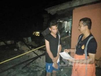 Mahusin Hassan (kanan) sedang mendapatkan maklumat daripada Aliah Ismail (kiri) di tapak kebakaran di Kampung Tebing Tinggi, Sabak.