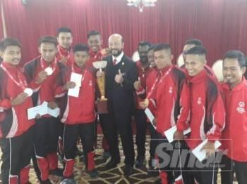 Mukhriz (tengah) bergambar bersama pasukan bola sepak Persatuan Olimpik Khas Kedah selepas majlis penghargaan di Wisma Darul Aman hari ini.