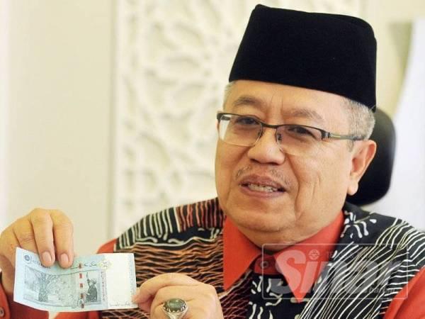 Datuk Mohamad Nordin Ibrahim menunjukkan wang kertas Malaysia yang mempunyai tulisan jawi. Foto: ROSLI TALIB