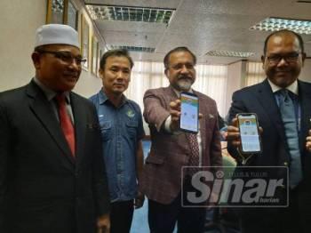 Dari kiri, Rozali, Jagdeep, Tung Seang dan Abdul Halim menunjukkan aplikasi PSP yang dimuat turun ke dalam telefon bimbit pada sidang media tadi.