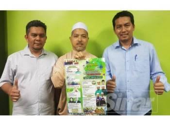 Nik Nasri (tengah) menunjukkan poster program Sambutan 1 Tahun Pemerintahan Pas Terengganu Peringkat Pas Kawasan Kemaman yang akan berlangsung mulai esok.