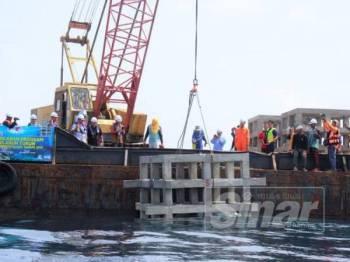 Azman (tengah) menyaksikan kerja menurunkan tukun dasar lembut di perairan Setiu hari ini.