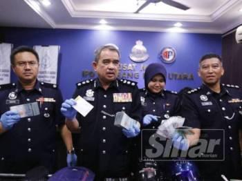 Noorzainy (tengah) menunjukkan wang tunai yang dirampas dari suspek selepas dipercayai merancang kejadian samun Ahad lalu.