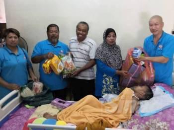 Pui (kanan) menyerahkan keperluan harian Faiz kepada ibunya, Sarimah (dua, kanan) ketika lawatan mereka ke rumah murid itu di Taman Tiong hari ini.