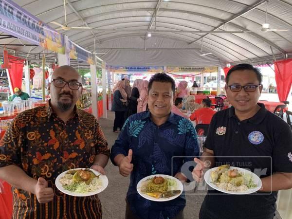 Mohd Aidil Afizie (kanan) menunjukkan Nasi 100 yang perlu dicuba kerana kelainan rasanya pada Festival Makanan dan Warisan Asean Kelantan 2019 di pekarangan Stadium Sultan Muhammad IV.